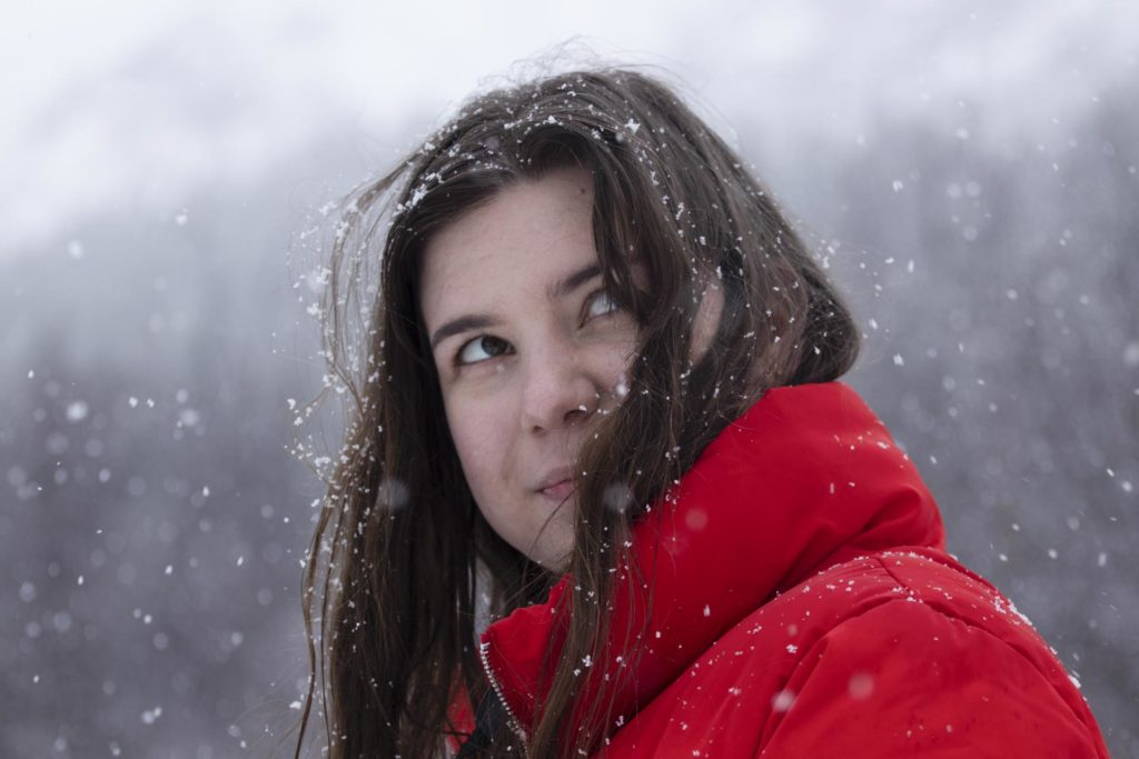 Portrait of young woman in winter with red jacket