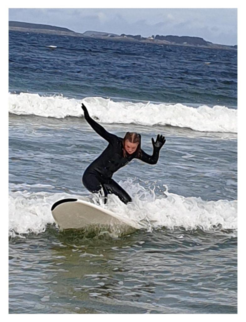 Jente surfer i blågrønt hav