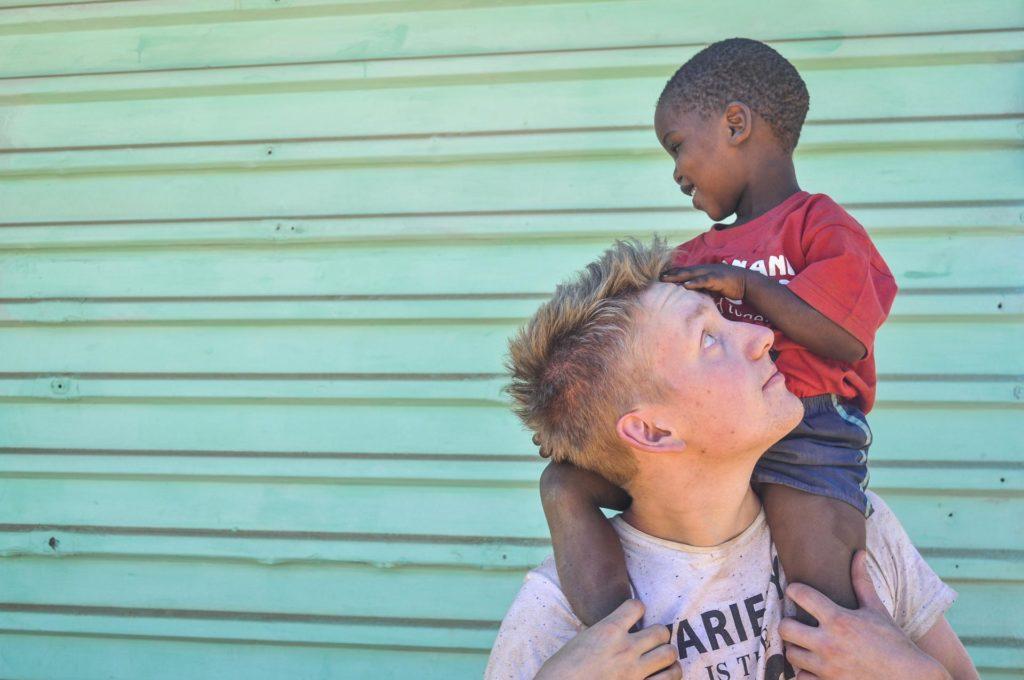 Ung mann med barn på skuldrene