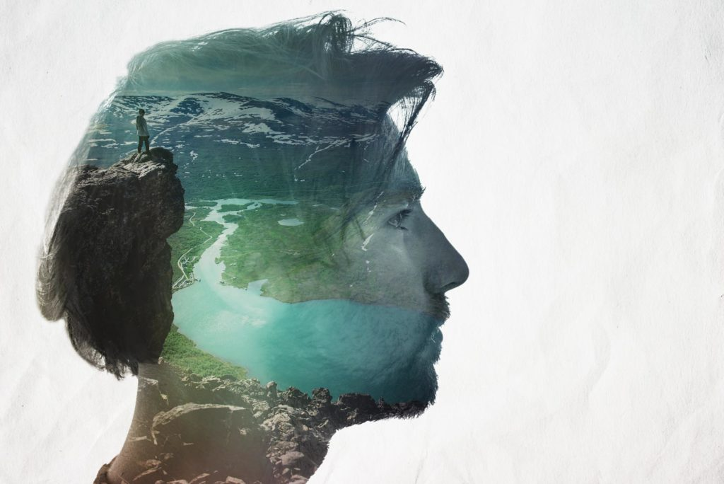 Double exposure of young man and mountain view
