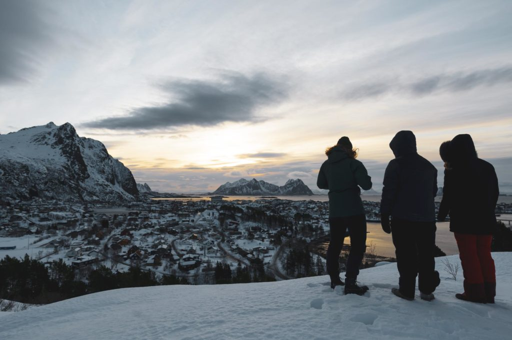 Three young people in front of a view of the sea and mountains in Lofoten