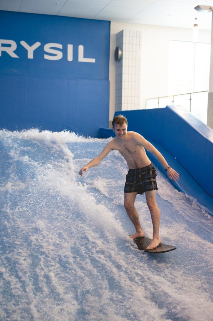 Young man surfing indoors on FlowRider