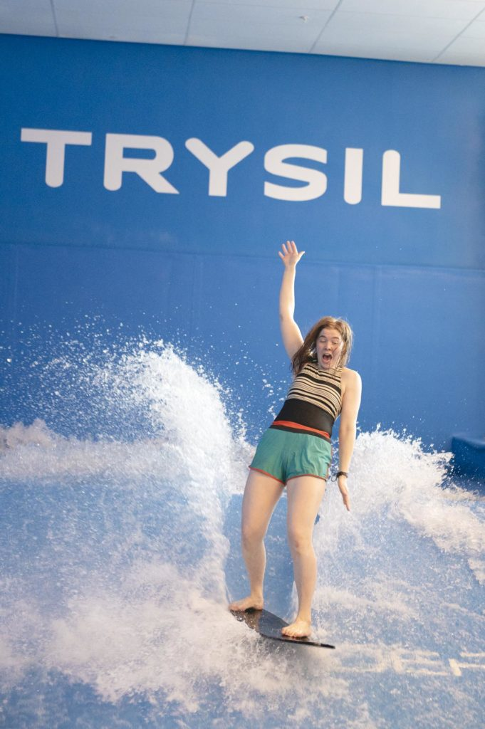 Young woman surfing indoors on FlowRider