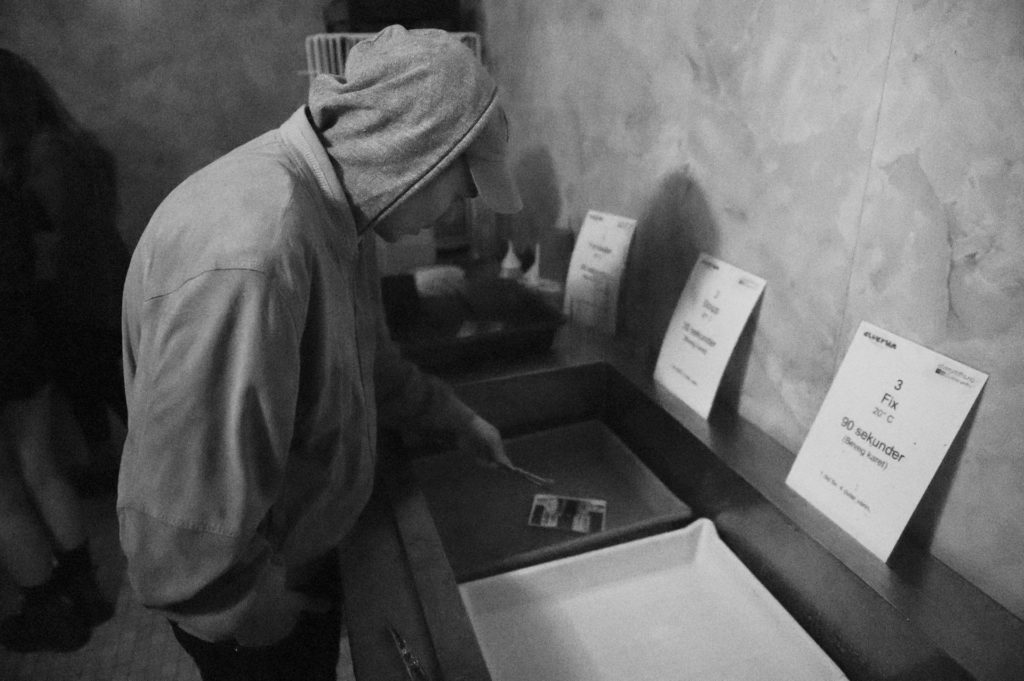 Young man with hood working in darkroom