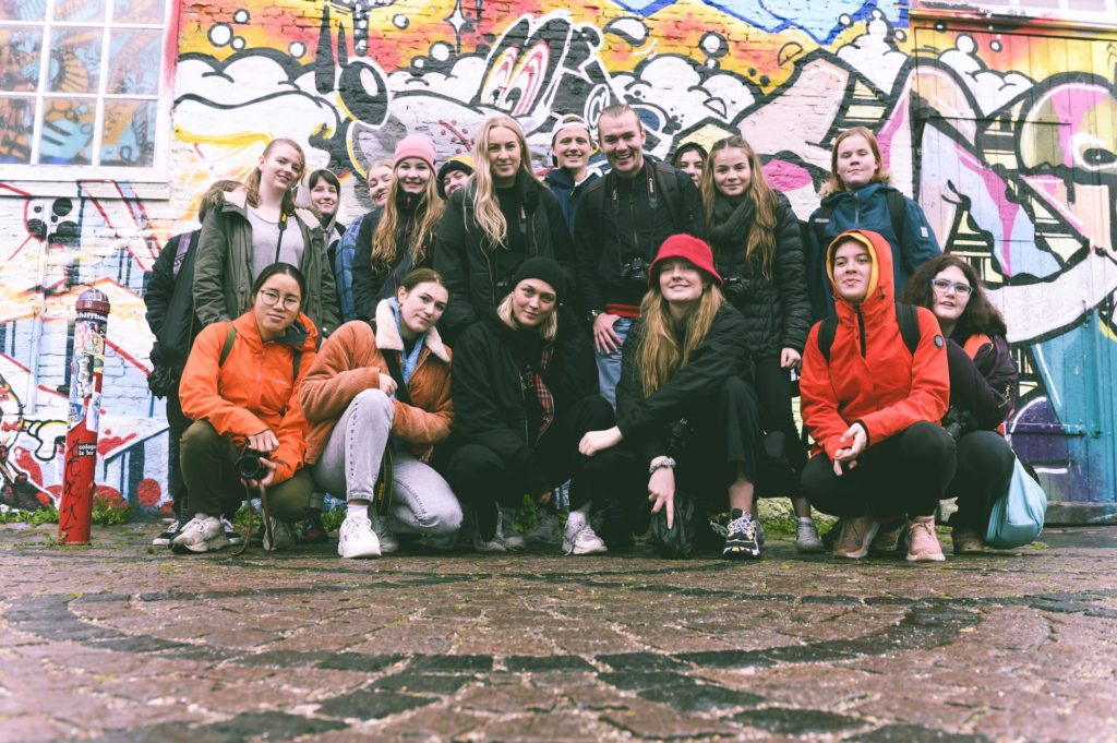 Group photo of young people in front of graffiti