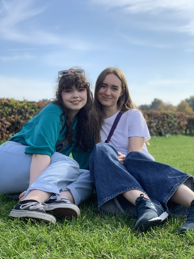 Two smiling young women in park