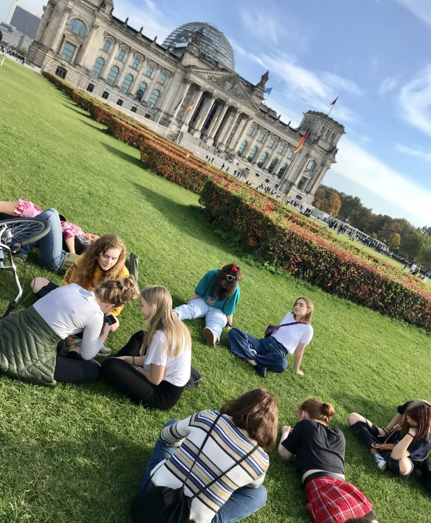 Young people in a park in front of the Reichstag in Berlin