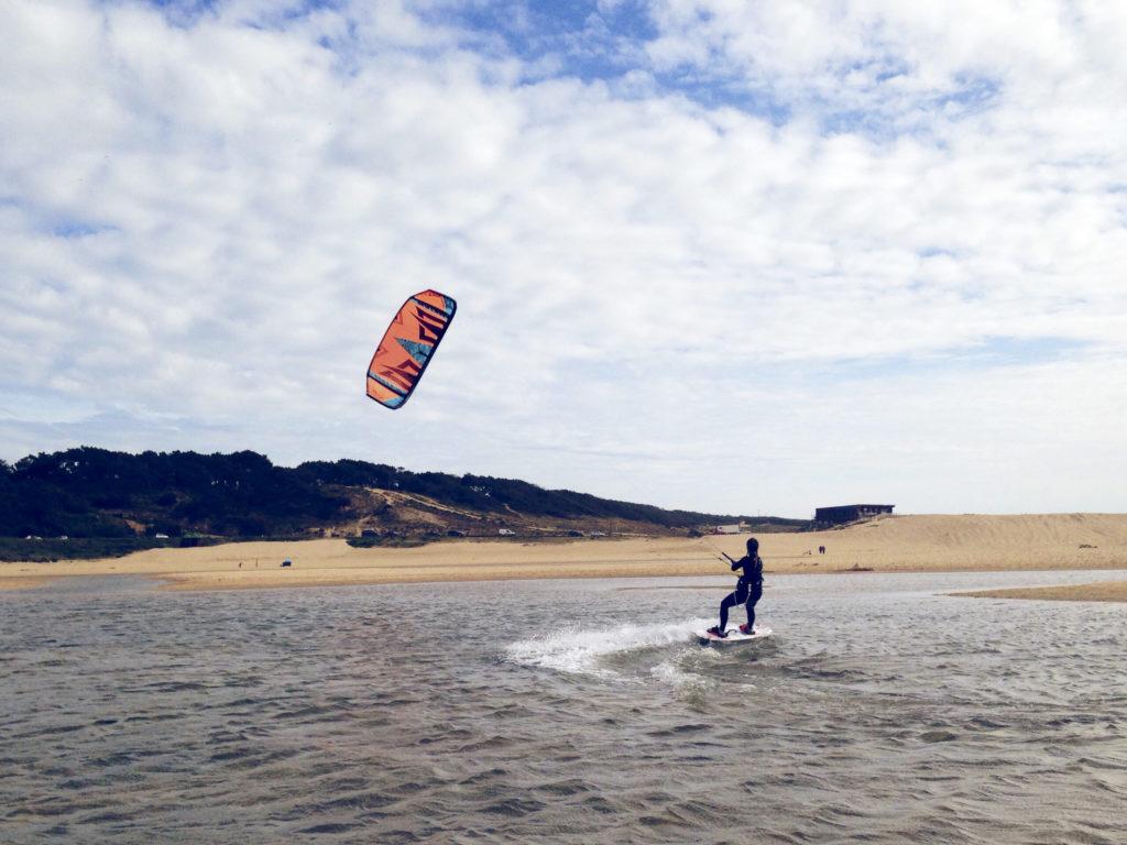 Kiteboarder på vann mot sandstrand
