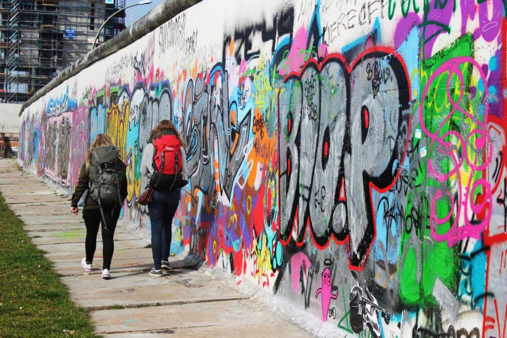 Backpackere langs graffitivegg