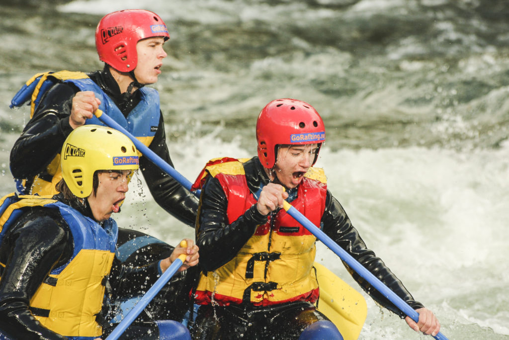 Expressive faces of young people rafting