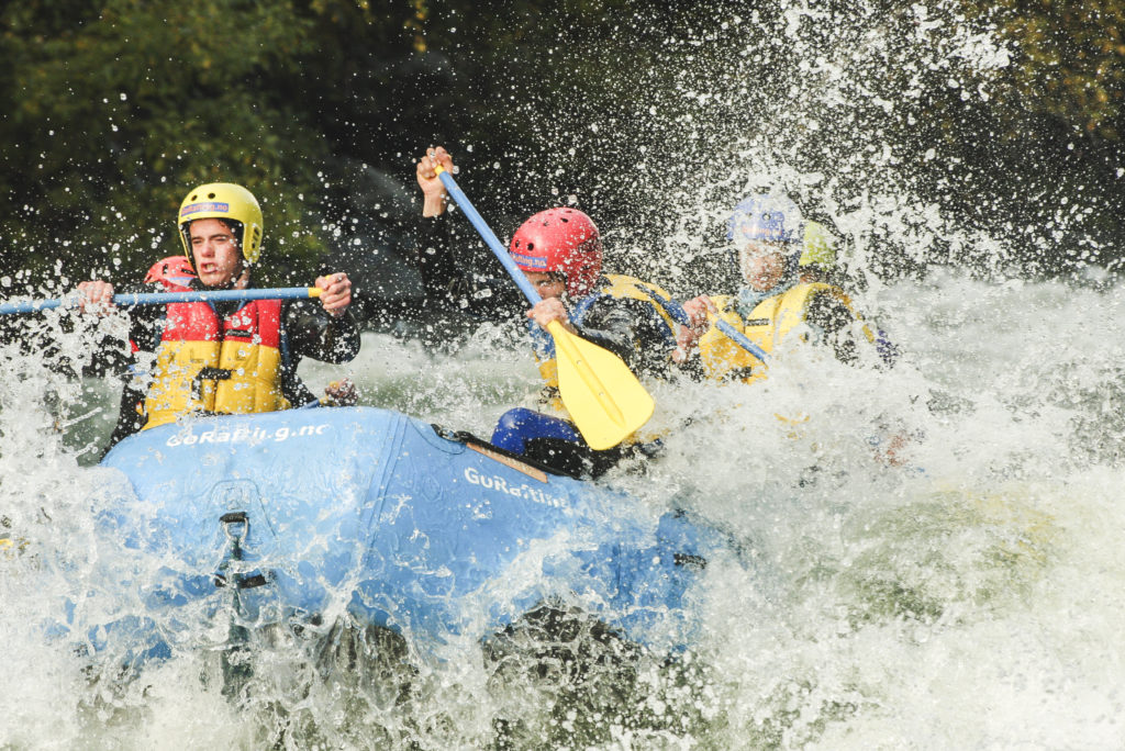 Rafting boat in water spray