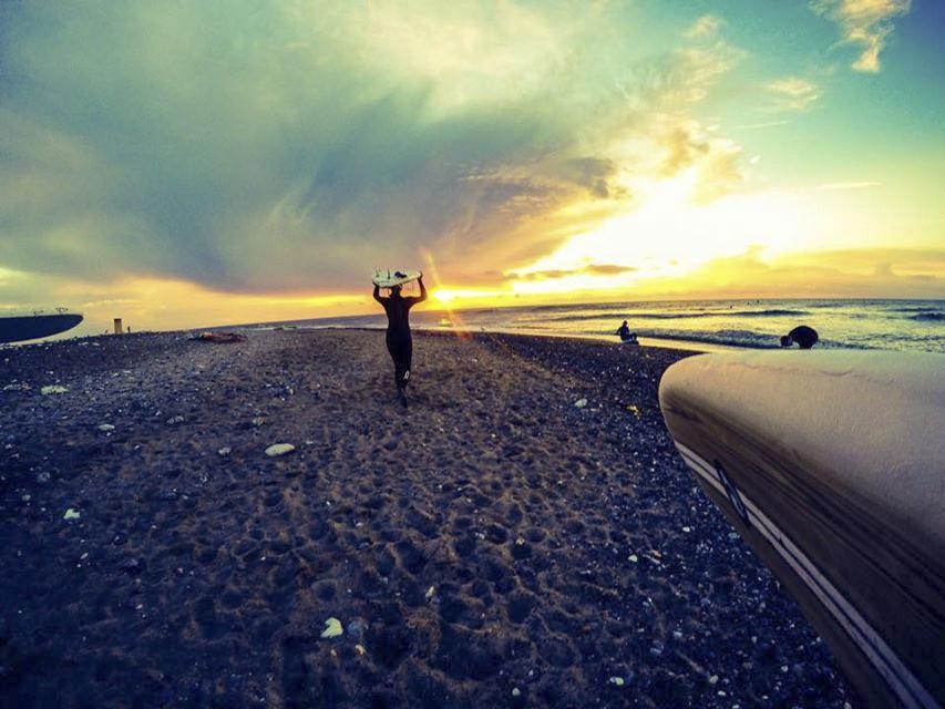 Surfer bærer brett på hodet i solnedgang