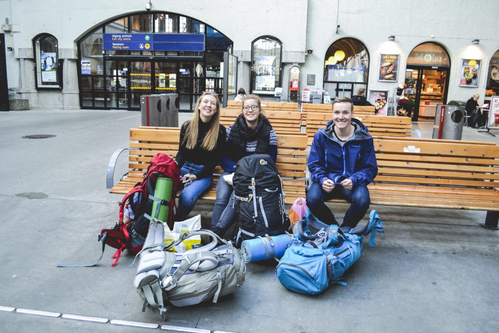 Backpackere smiler mens de venter på togstasjon