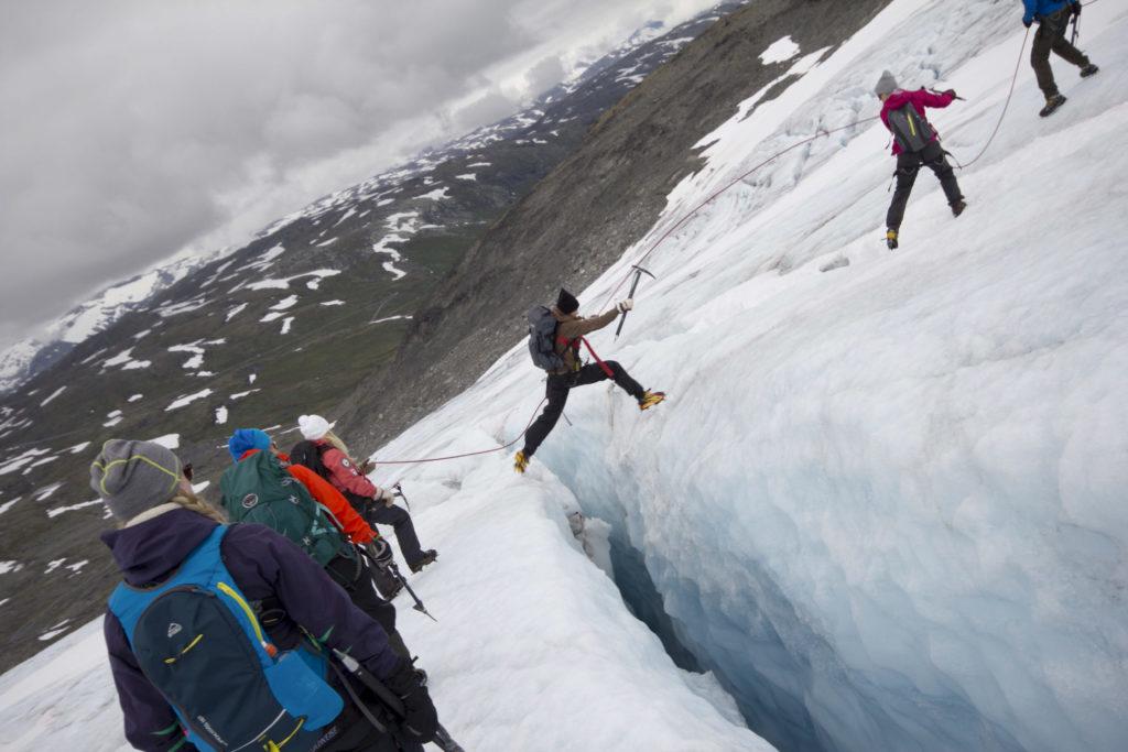 Person skips glacier crack on glacier change