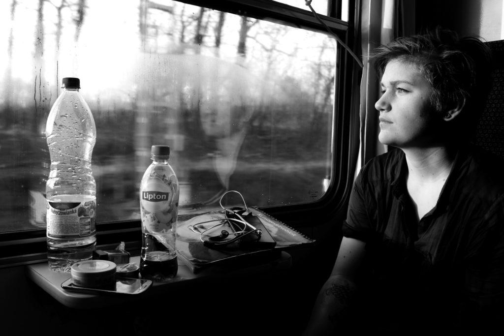 Ung kvinne ser ut av vinduet på tog på interrail
