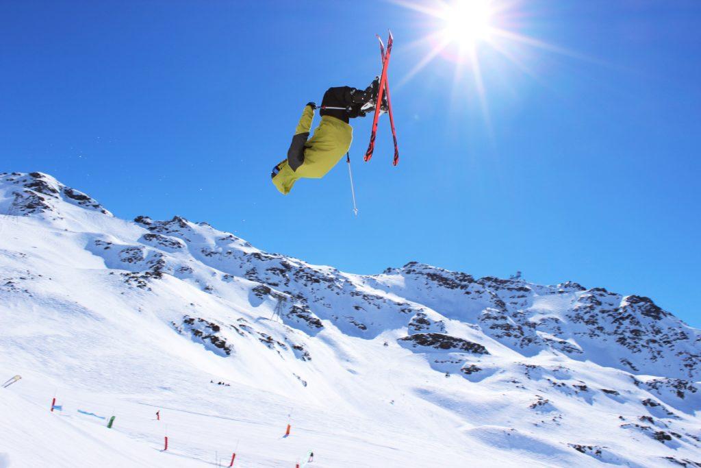 Skikjører trikser på hopp i alpefjell