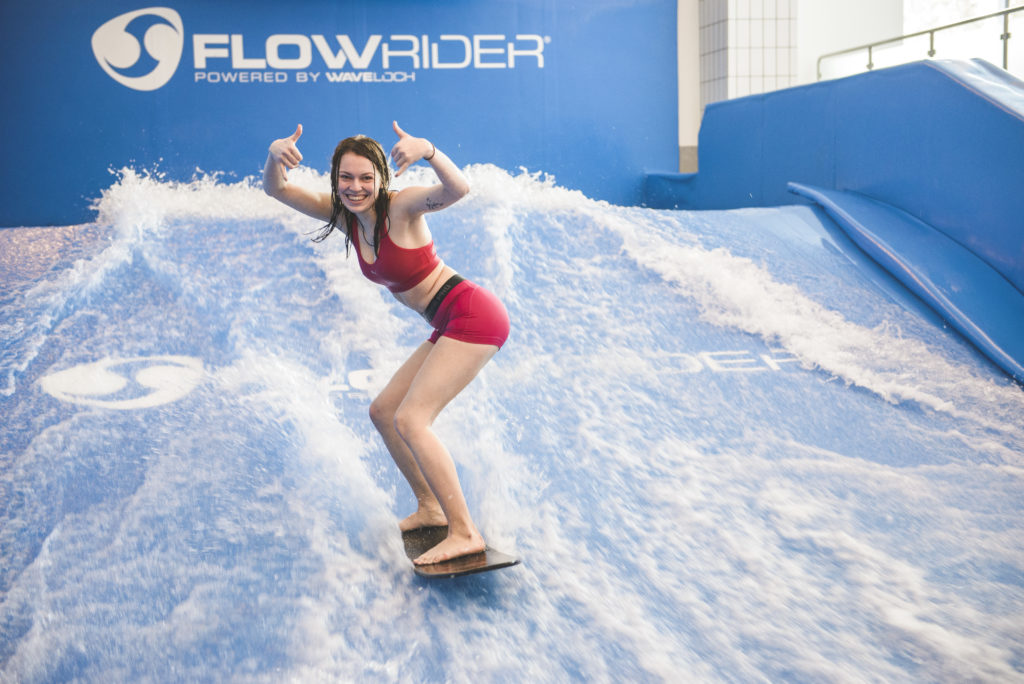 Young woman posing on indoor surfboard