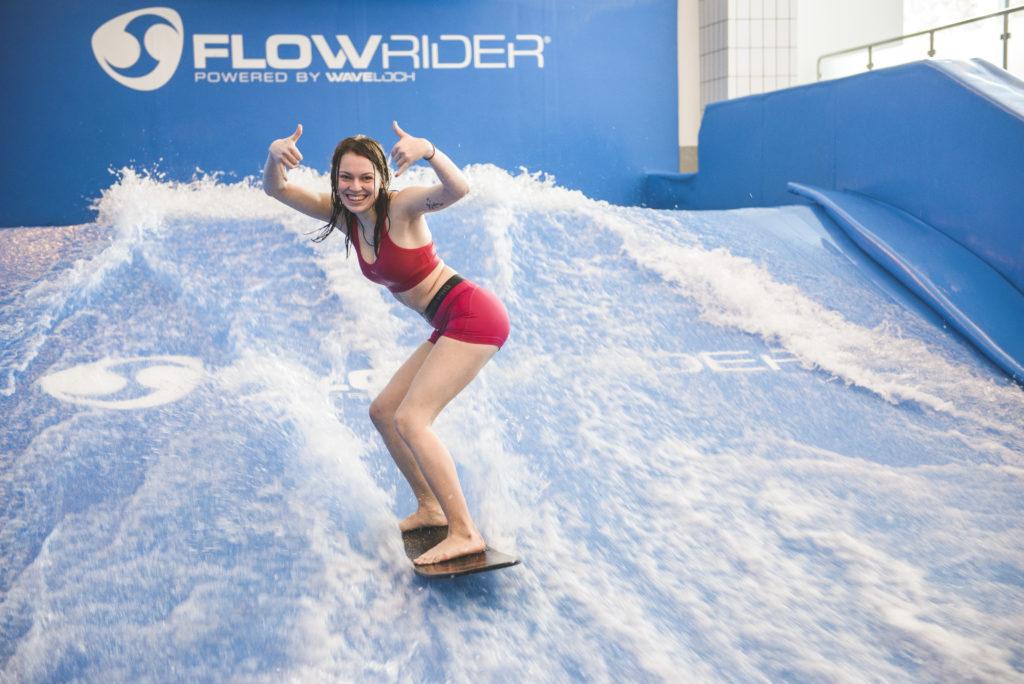Ung kvinne poserer på innendørs surfebrett