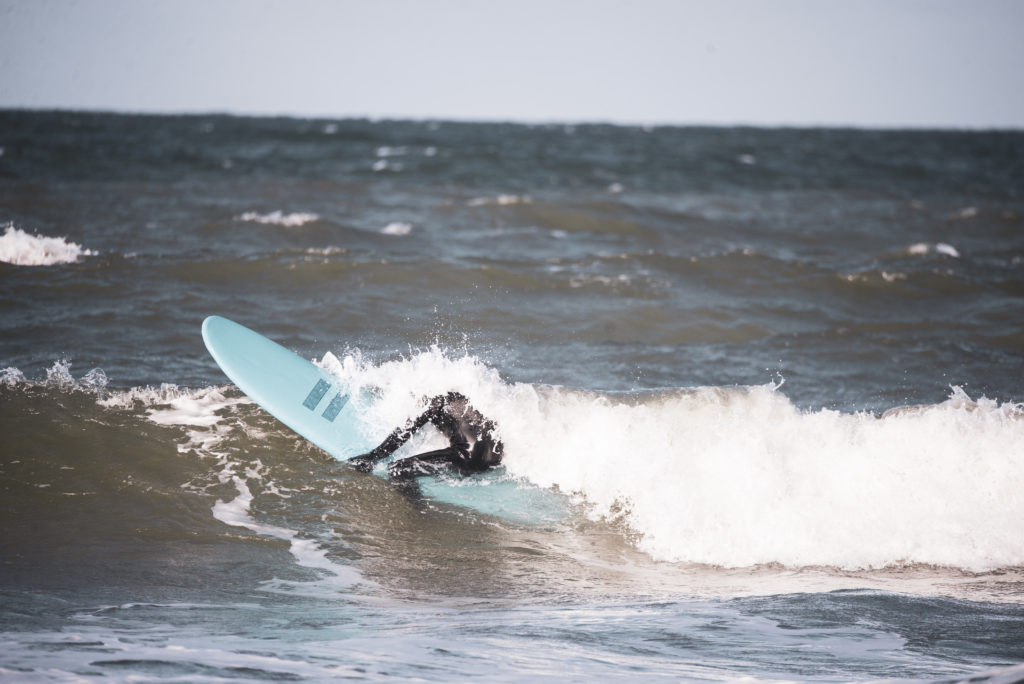 Person on surfboard pops through wave