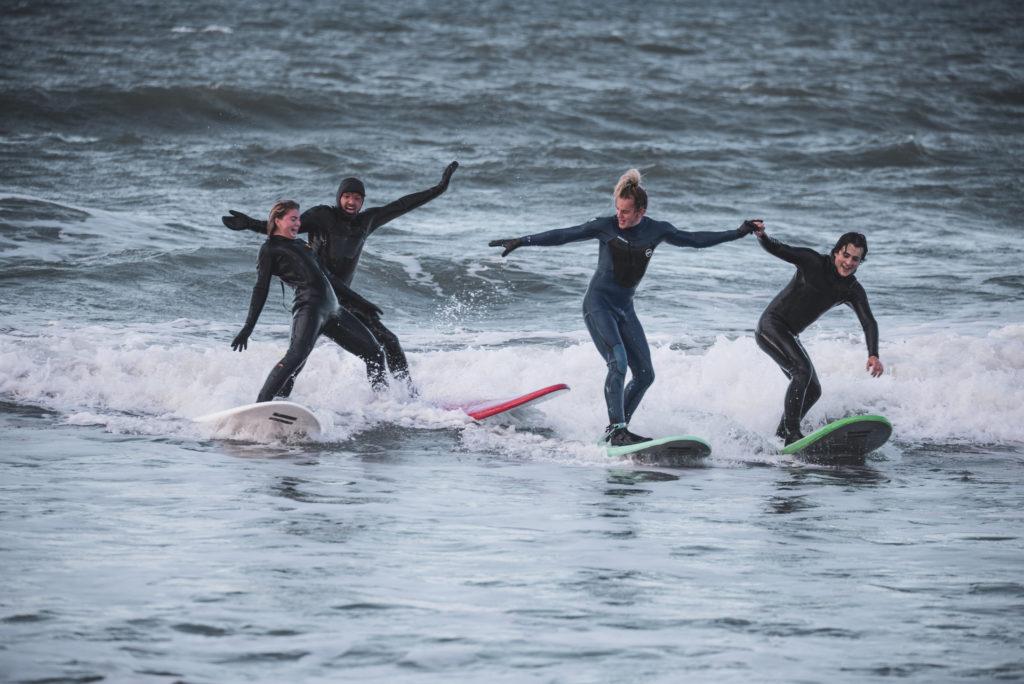 Unge mennesker på surfebrett i «partybølge»