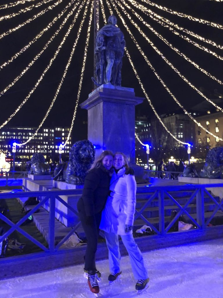 To unge kvinner poserer foran en skulptur med julebelysning