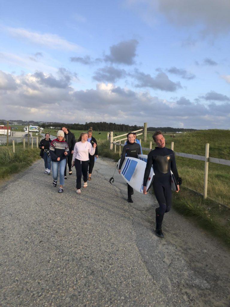 Gruppe unge mennesker på vei til stranda med surfebrett