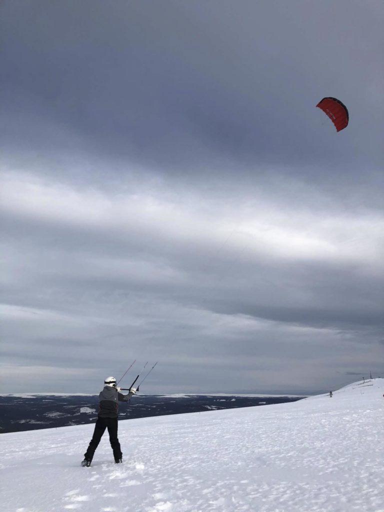 Person holder kite på snøkledd fjell