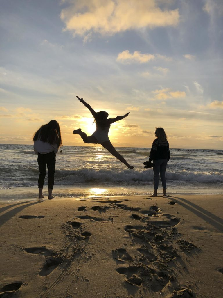 Silhouettes of young people jumping on the beach at sunset