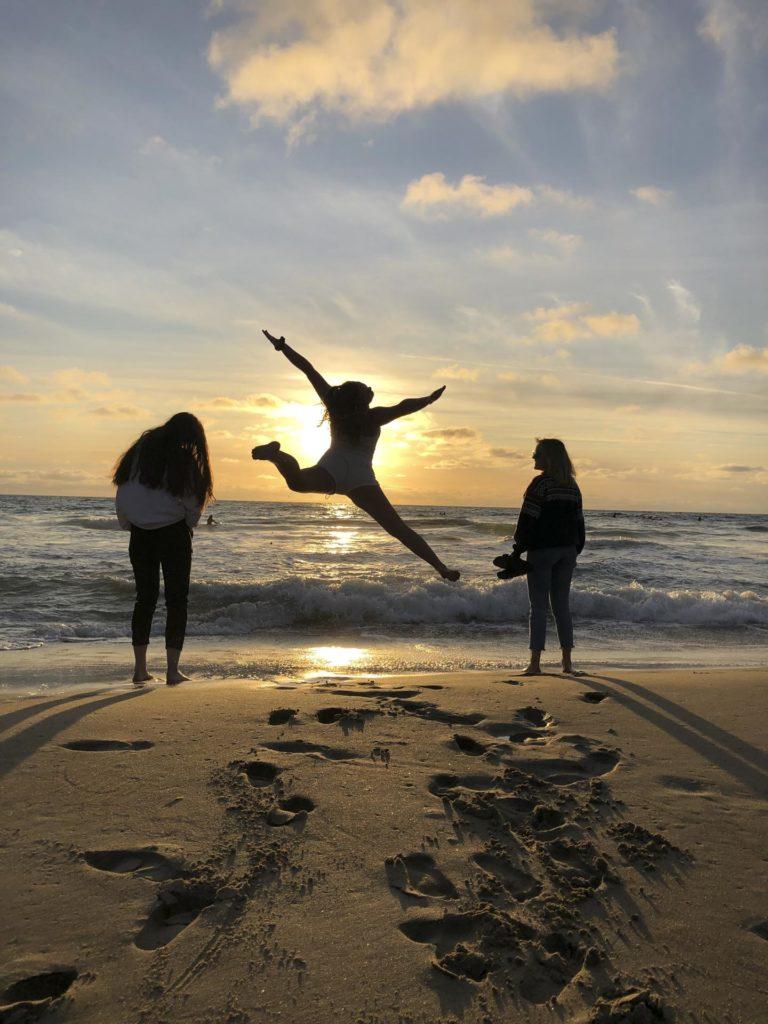 Silhuetter av unge mennekser hopper på stranda i solnedgang