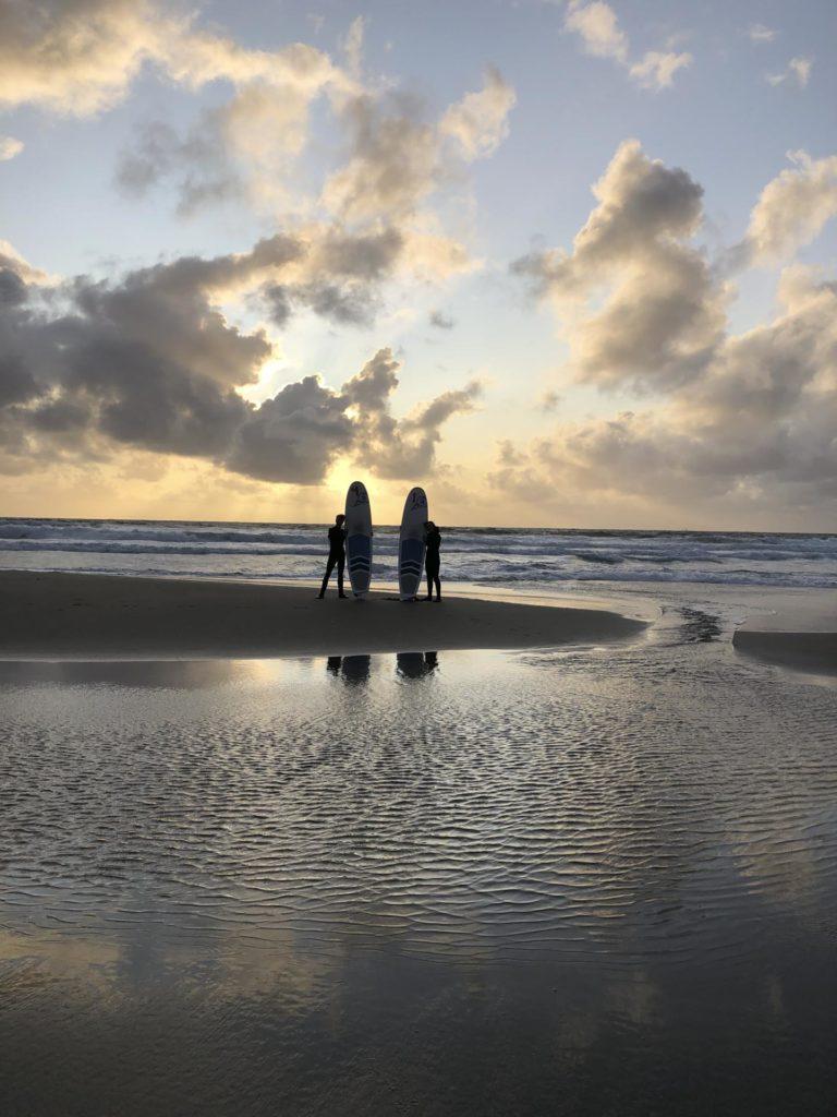 Silhuetter med surfebrett på en strand i solnedgang