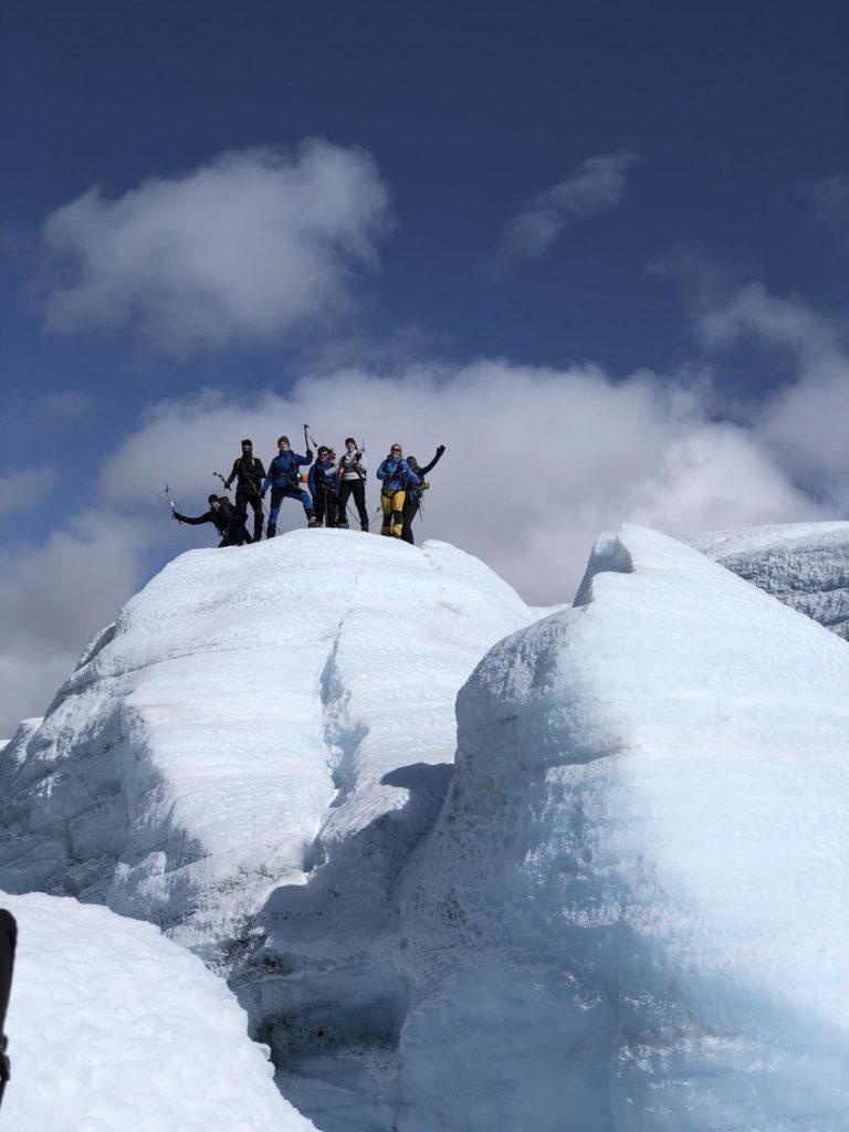 Gruppe unge mennesker på toppen av en isformasjon
