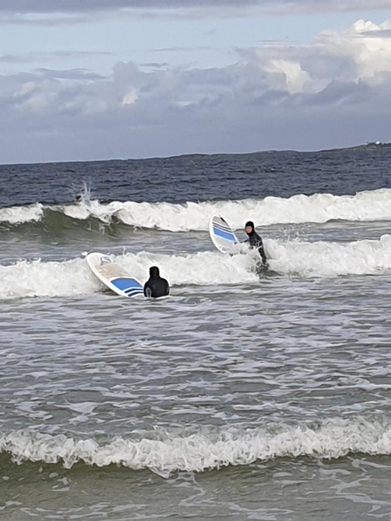 Two people on a surfboard paddle out to sea