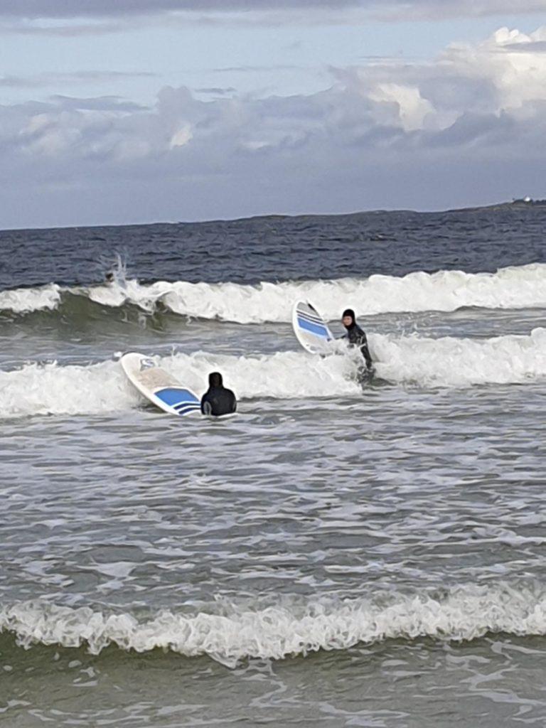 To personer på surfebrett padler ut i havet