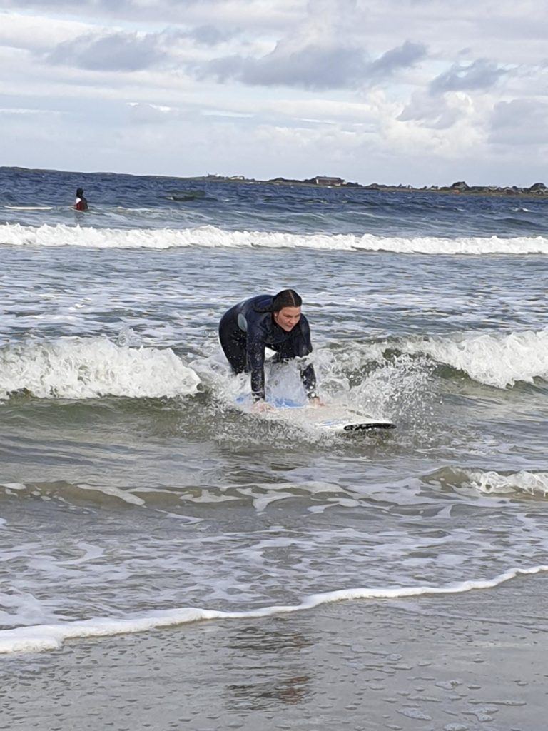 Person trying to get up on surfboard in wave