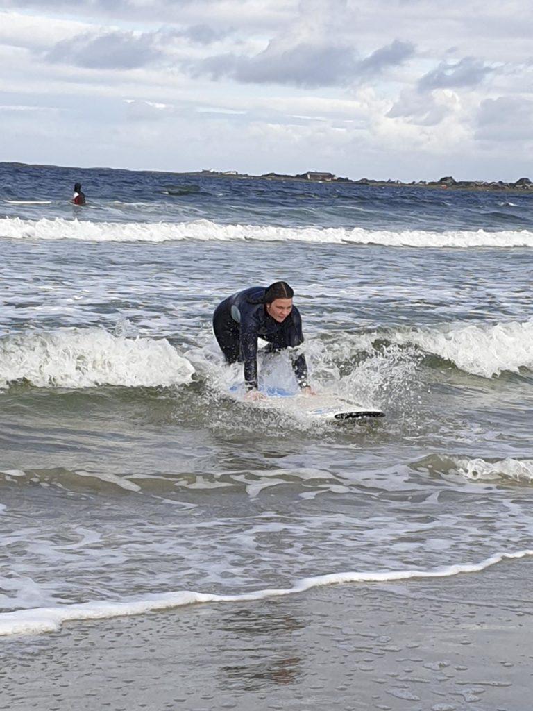 Person prøver å reise seg på surfebrett i bølge