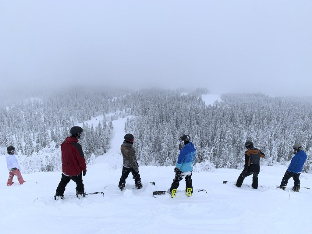 Four young people look out over a ski resort full of powder snow