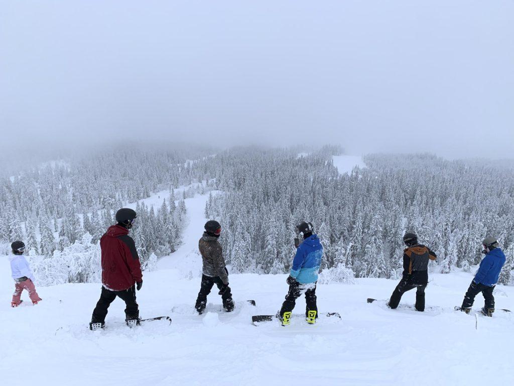 Fire unge mennekser skuer utover et skianlegg fult av puddersnø