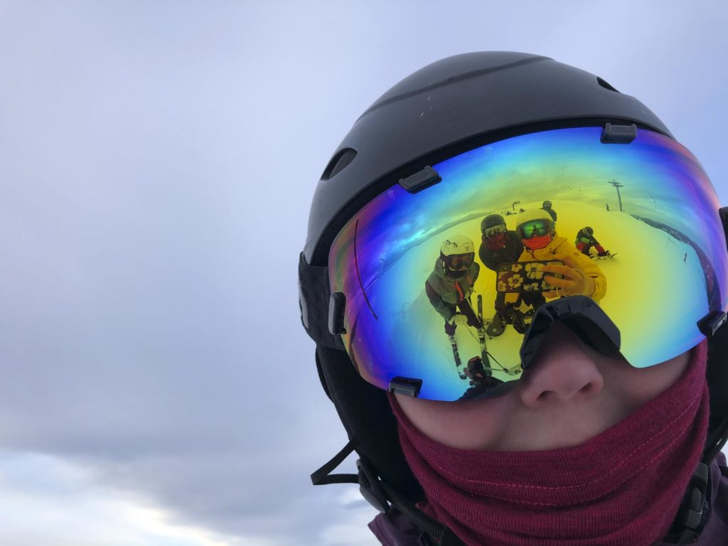 Selfie in ski goggles with reflection of other young people