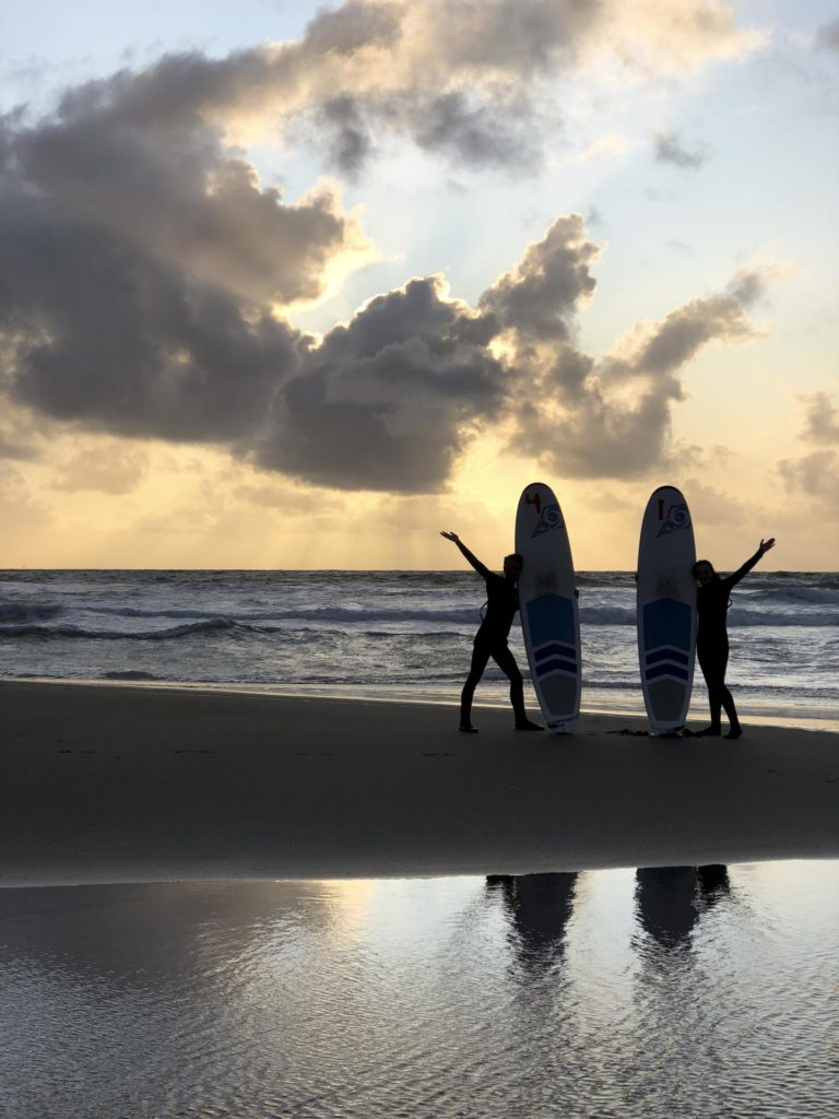 Silhouettes with surfboards on a beach at sunset