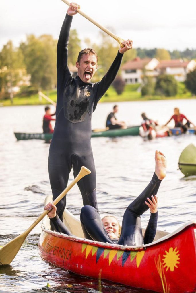 Young man cheering in canoe
