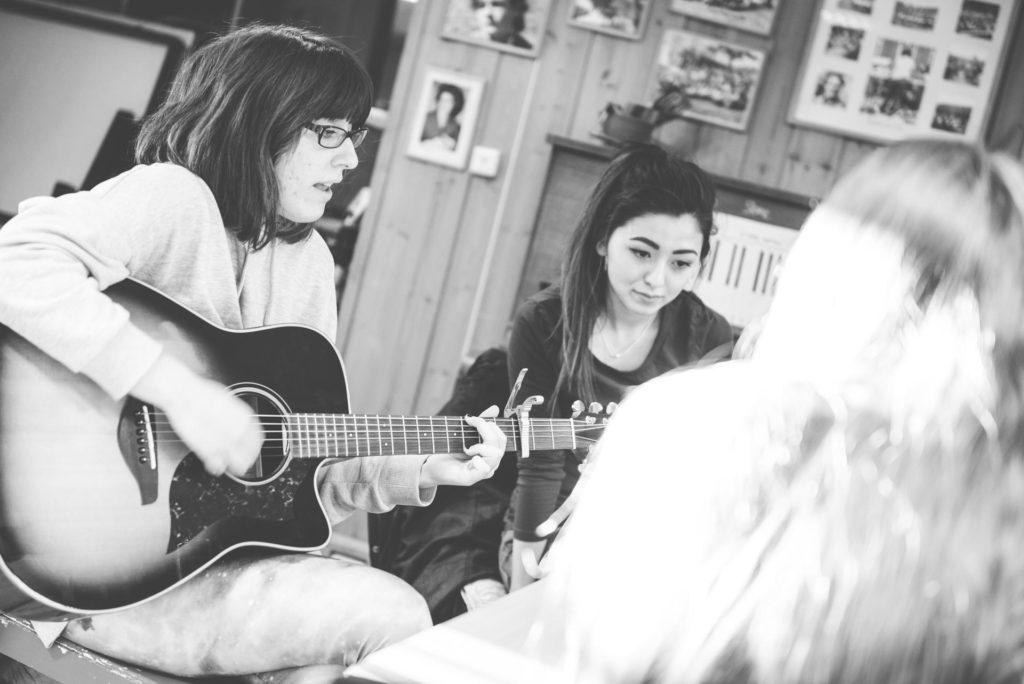 Unge kvinner øver på gitar og sang