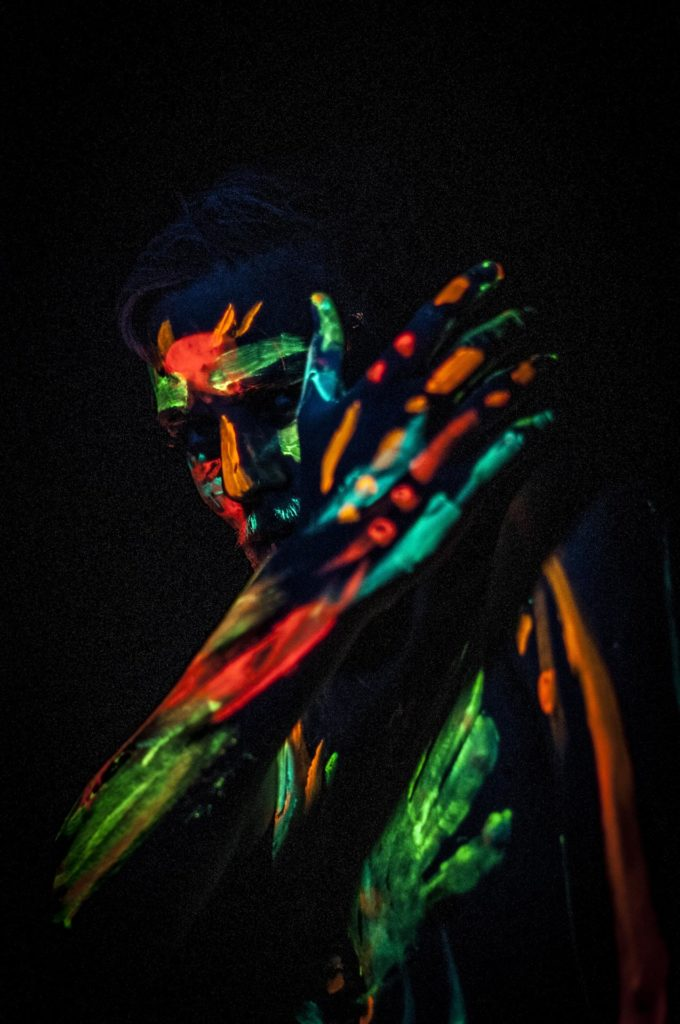 Person decorated with luminous colors in the photo studio