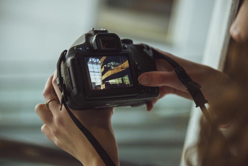 Hender holder kamera med bilde av moderne arkitektur