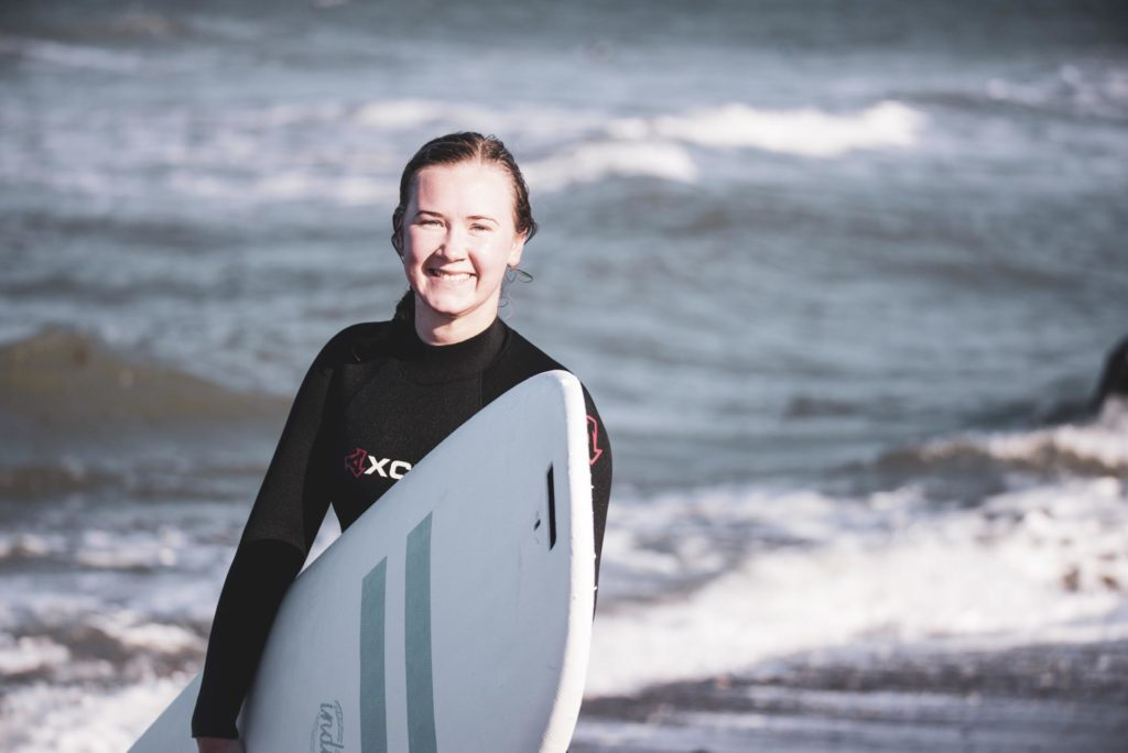 Young woman holding surfboard