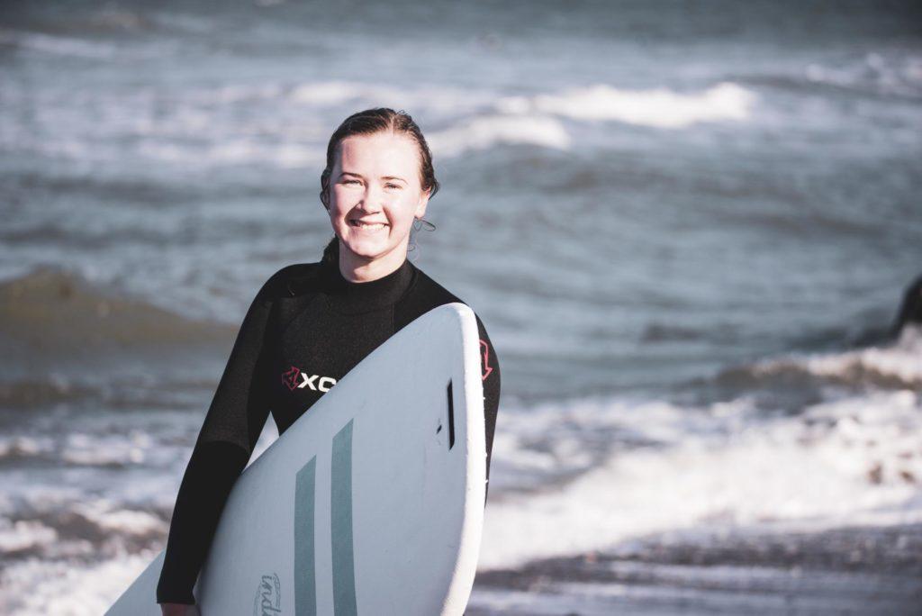 Ung kvinne holder surfebrett