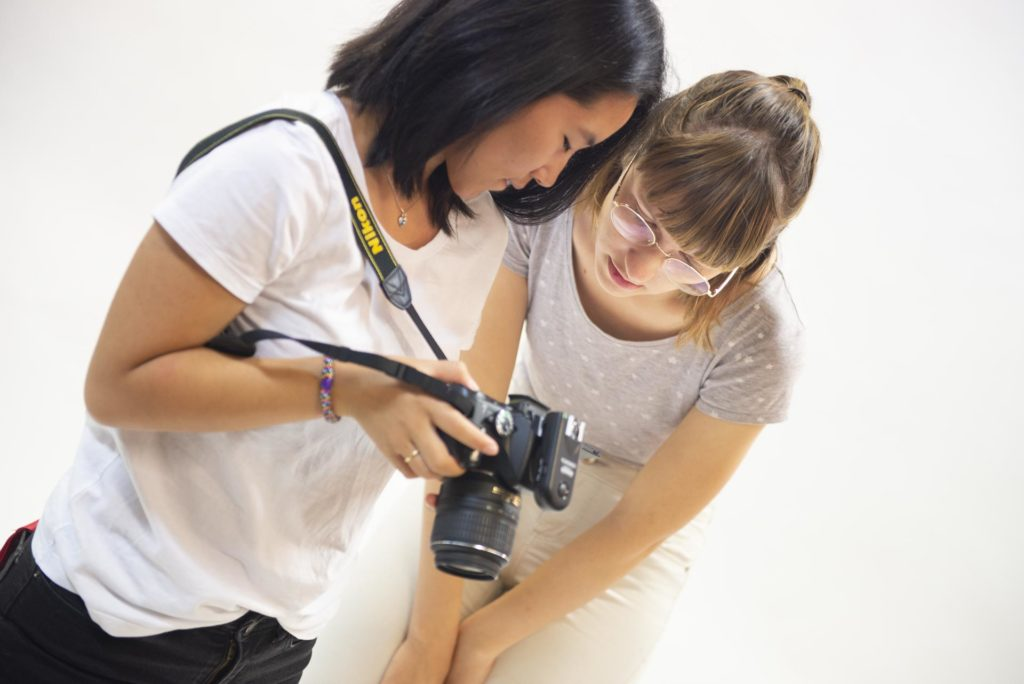 Two young women looking at a photo camera in a photo studio