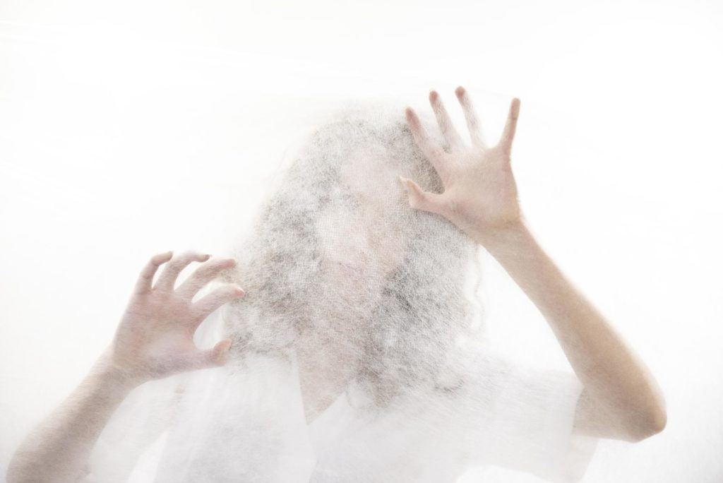 Hands pressing against white fabric