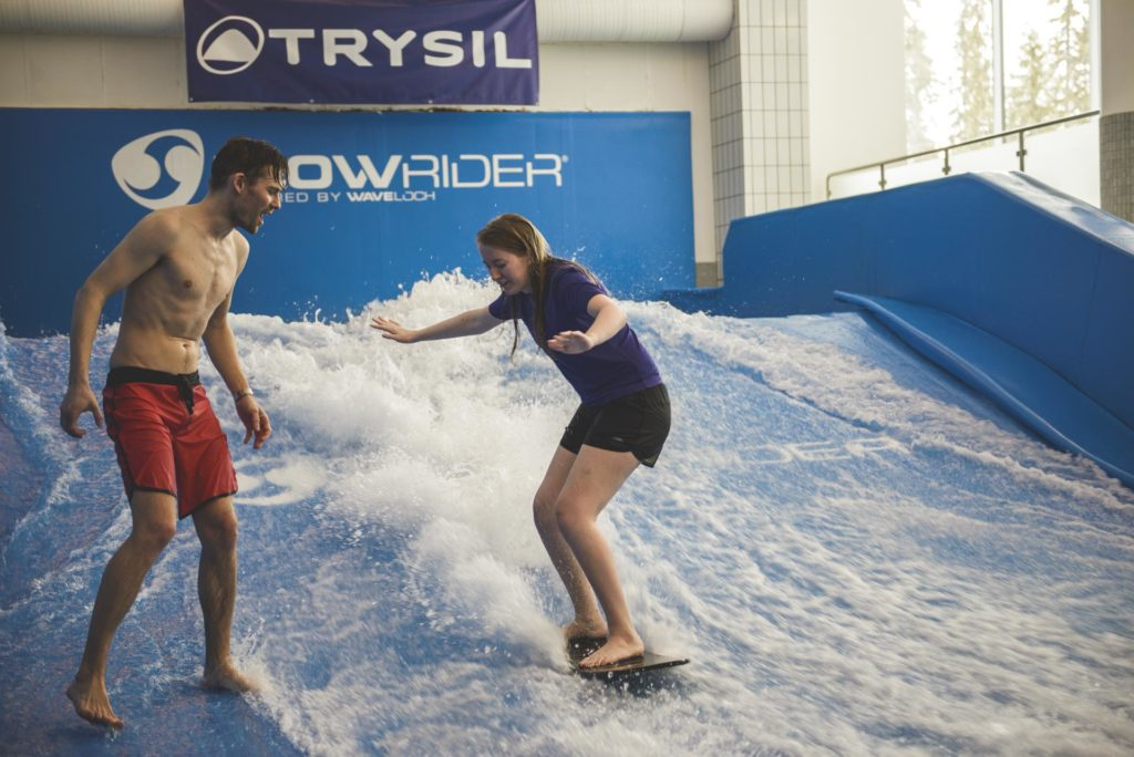 Young woman trying indoor surfing on FlowRider