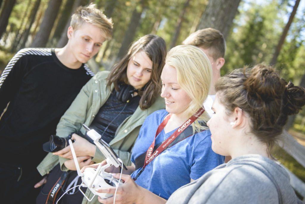 Unge mennesker ser på mens de flyr drone