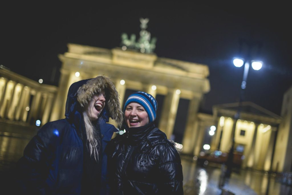 Two young women laugh in front of the Brandenburg Gate